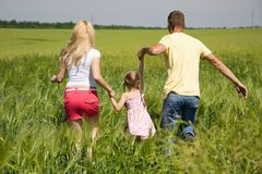 Young family running across the field Royalty Free Stock Photos
