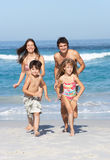 Young Family Running Along Beach on Holiday. Smiling At Camera Royalty Free Stock Photography