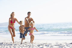 Young Family Running Along Beach on Holiday Stock Photo