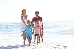 Young Family Running Along Sandy Beach On Holiday Stock Photo