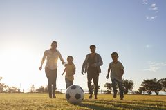 Young family running after a football in a park Stock Photos