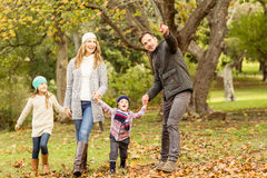 Young family running in leaves Royalty Free Stock Photo