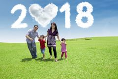 Young family running with numbers 2018. Young family playing together while running in the park with clouds shaped heart and numbers 2018 in the sky stock images
