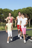 Young Family Running On Road Royalty Free Stock Images