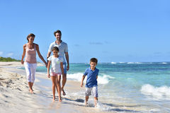 Young family running on the seaside Royalty Free Stock Images