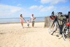 Young family running to the bicycles. Happy family running on a sandy beach Stock Images