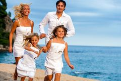 Young family running together. Young couple running together with kids on beach Royalty Free Stock Photography