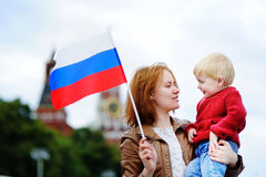 Young family with russian flag with Moscow Kremlin on background Stock Photos