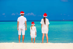 Young family in Santa hats relaxing on tropical beach during Christmas vacation Royalty Free Stock Photos