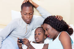 Young family sharing a cell phone in bed. This young couple watching their child play with the mobile phone stock images