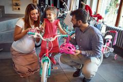 Young family shopping new bicycle for little girl in bike shop. Young family shopping new bicycle for happy little girl in bike shop stock photos