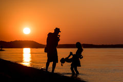 Young Family. Silhouette of a young family have fun on beach at sunset Stock Photo