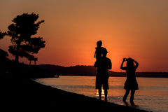 Young Family. Silhouette of a young family have fun on beach at sunset Royalty Free Stock Photo
