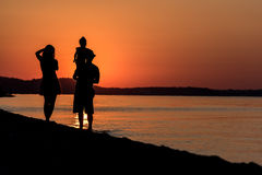 Young Family. Silhouette of a young family have fun on beach at sunset Stock Photography