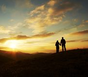 Young family silhouette for sunset. Girl and boy silhouette on the sunset background Stock Photography