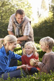 Young family sit together in garden Royalty Free Stock Image
