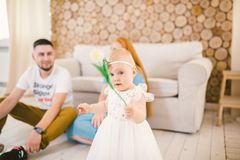 Young family sits on the floor near the couch,small daughter of a blonde one year old is learning to walk in a white dress against Royalty Free Stock Photography