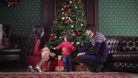 Young family sits near the rich Christmas tree. It is decorated garland, toys, ribbons, bows. Mom, Dad and their little stock video footage