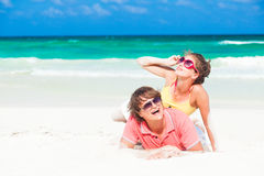 Young family sittin on beach and having fun Royalty Free Stock Images
