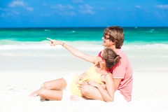 Young family sittin on beach and having fun Stock Photos