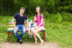 Young family sitting on a bench in the summer park Stock Photos