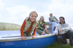 Young family sitting in boat at beach Stock Photos