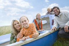 Young family sitting in boat at beach Stock Photo