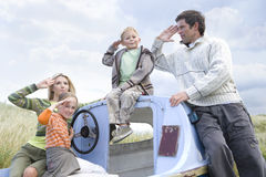 Young family sitting on boat at beach saluting Stock Photo