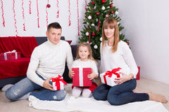 Young family sitting with gift boxes in front of Christmas tree Royalty Free Stock Photos
