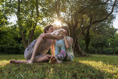 Young family sitting in a grass in park Royalty Free Stock Photos