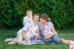 Young family sitting on the grass in a park with toys Royalty Free Stock Photo