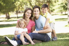 Young Family Sitting in Park Royalty Free Stock Photography
