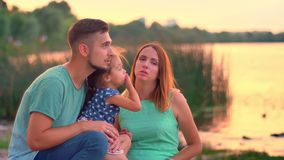 Young family is sitting in park on lake in summer, speaking, sunset, relax concept.  stock footage