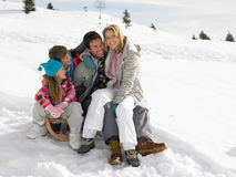 Young Family Sitting On A Sled In The Snow. All smiling looking at mother Royalty Free Stock Image