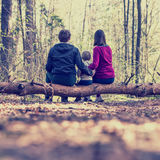 Young family sitting on a tree trunk Royalty Free Stock Image