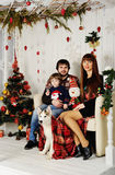 Young family sitting under the Christmas tree. Young family - mother, father and little boy sitting under the Christmas tree with a dog Husky Royalty Free Stock Image