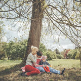 Young family is sitting under a tree Stock Images