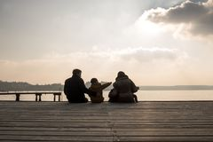 Young family with small children sitting on a deck Royalty Free Stock Image