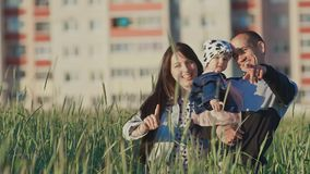 A young family with a small daughter in her arms in a field of wheat among the green spikelets. In the background of an. Urban building. Outskirts. Happy stock video