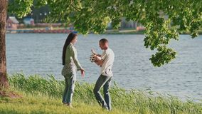 A young family with a small daughter, holding hands, runs along the path of a green park near the lake. Rest on the. Shore of the lake. Mom hugs her daughter stock video footage