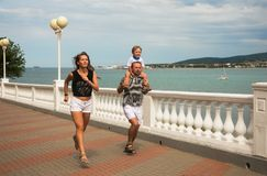 Young family small son jog along promenade sea Royalty Free Stock Photos