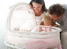 Young family smiling at baby in cot Stock Images