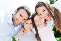 Young family smiling. Happy family smiling together outdoors