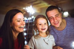 Young family with sparklers at Christmas time at home. Stock Photo