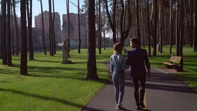Young family spend time at the open air sunny day autumnal day. Rear back view. People walking in park enjoy stroll. Casual woman and man talking and discussing stock video footage