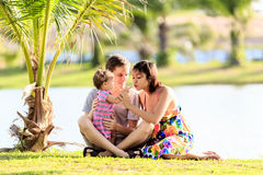 Young family spending time in a tropical garden Royalty Free Stock Images