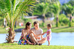 Young family spending time in a tropical garden Royalty Free Stock Photography
