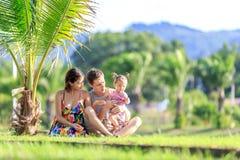 Young family spending time in a tropical garden Stock Photos