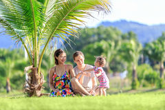 Young family spending time in a tropical garden Stock Photo