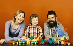 Young family spends time in playroom. Family and childhood. Concept. Parents and son with happy faces make brick constructions. Mom, dad and boy on red royalty free stock image